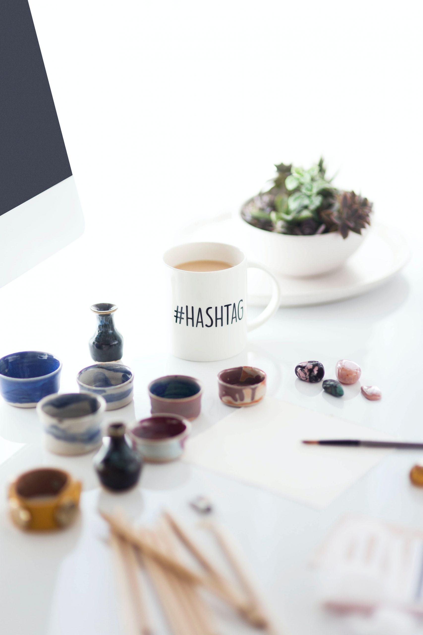 Hashtag en taza de café en mesa con pinturas=