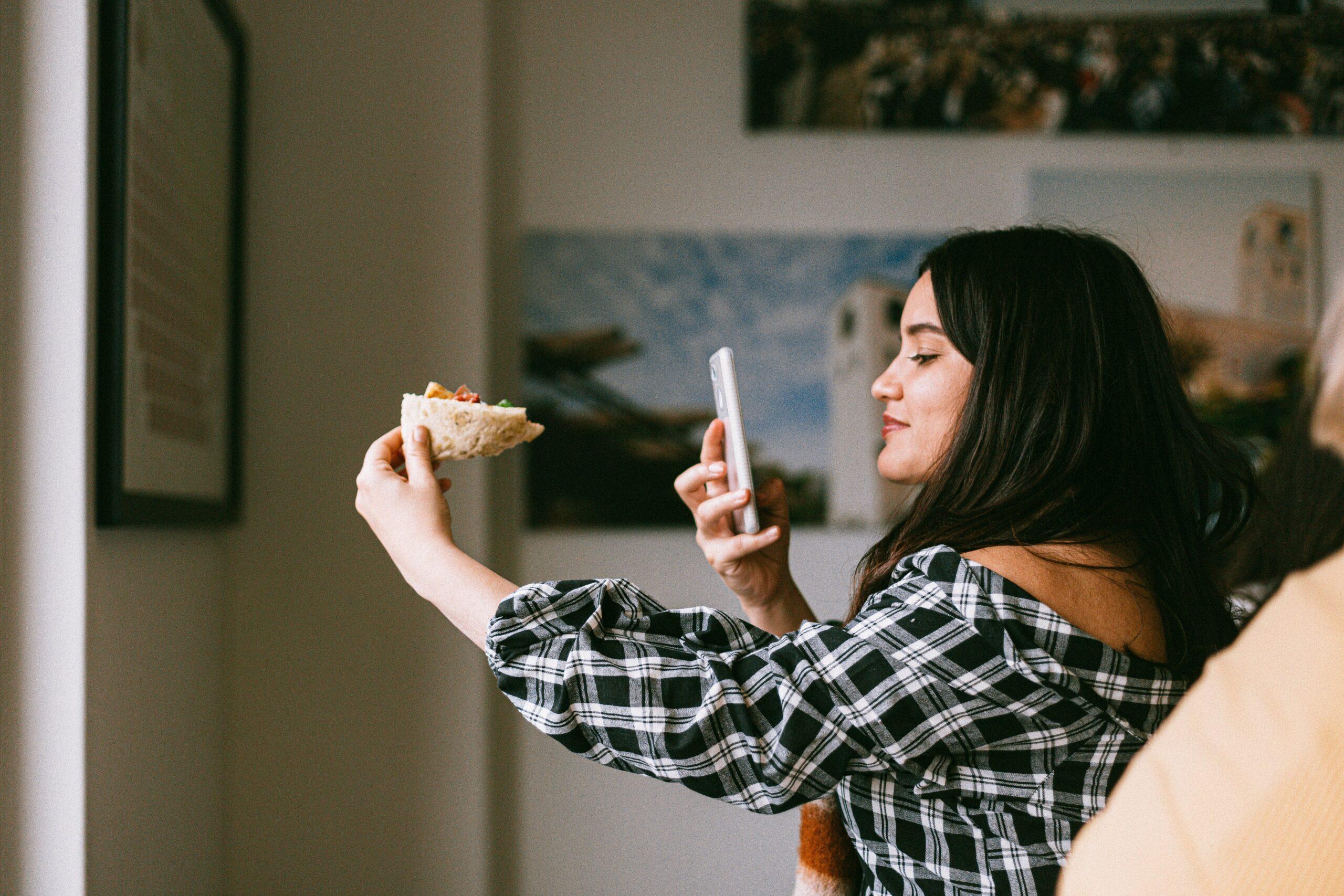 Chica influencer tomando foto a su comida con su móvil