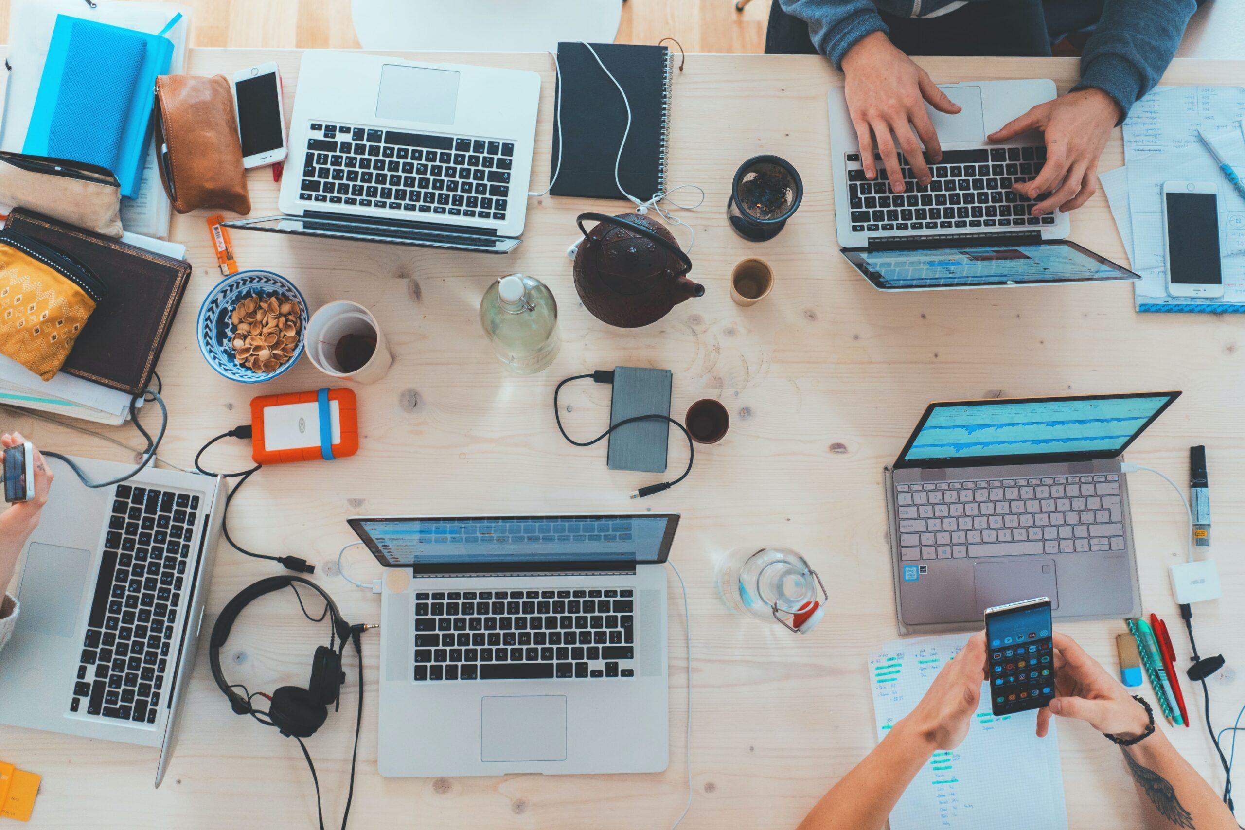 Equipo de trabajo de Marketing digital con ordenadores, móviles, escritorio