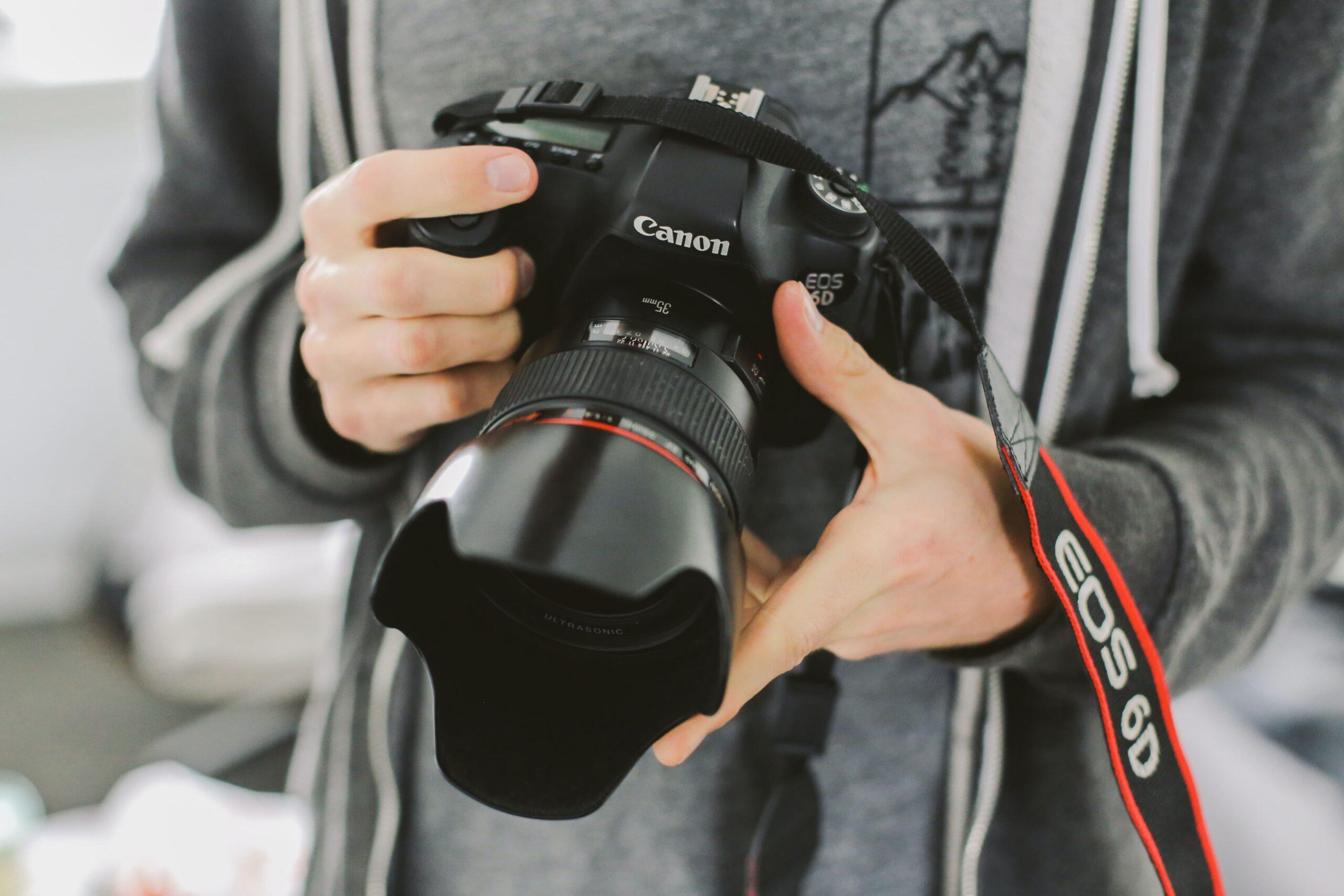 fotógrafo sosteniendo cámara profesional canon con las manos
