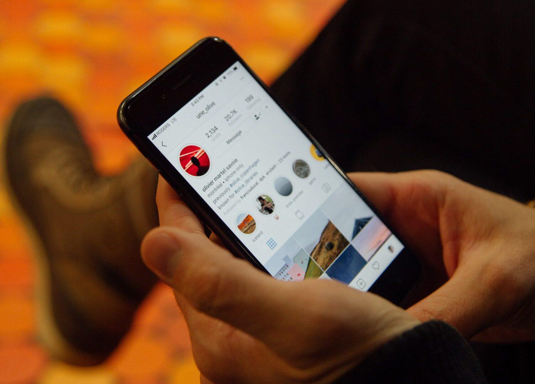 Hombre sostiene movil viendo feed de Instagram