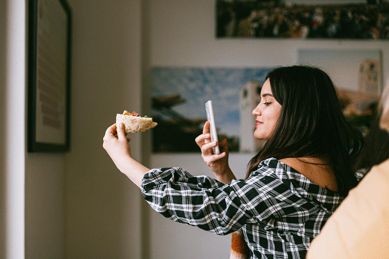 Chica influencer tomando foto a su comida