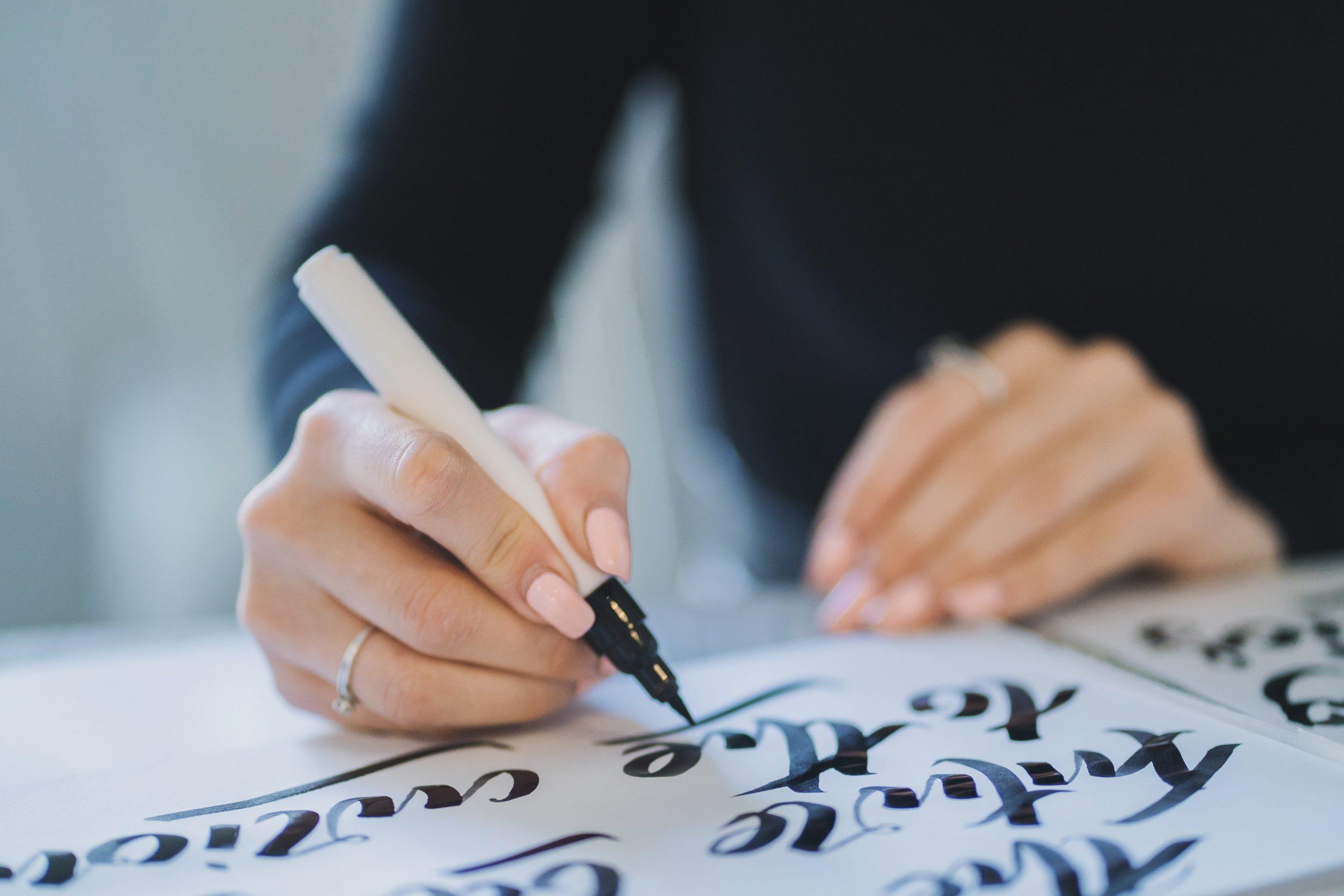 Mujer escribiendo con pluma frases para ganar seguidores en instagram