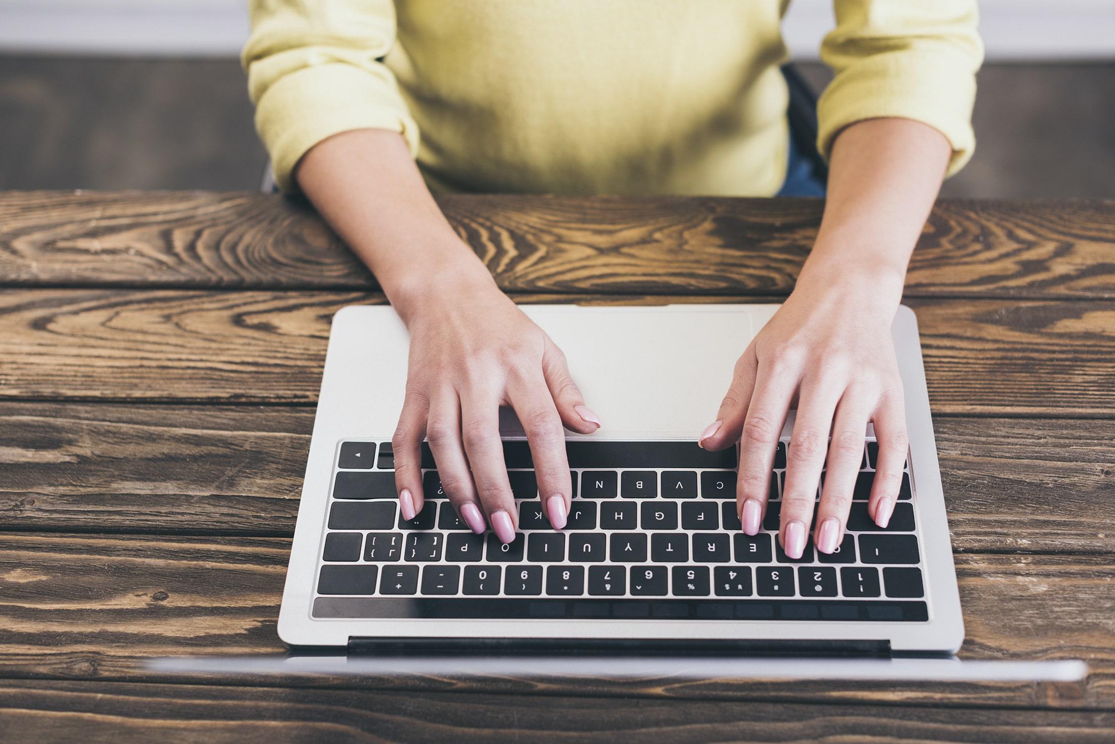 Escritora usando su ordenador portátil - Frases para ganar seguidores en Instagram