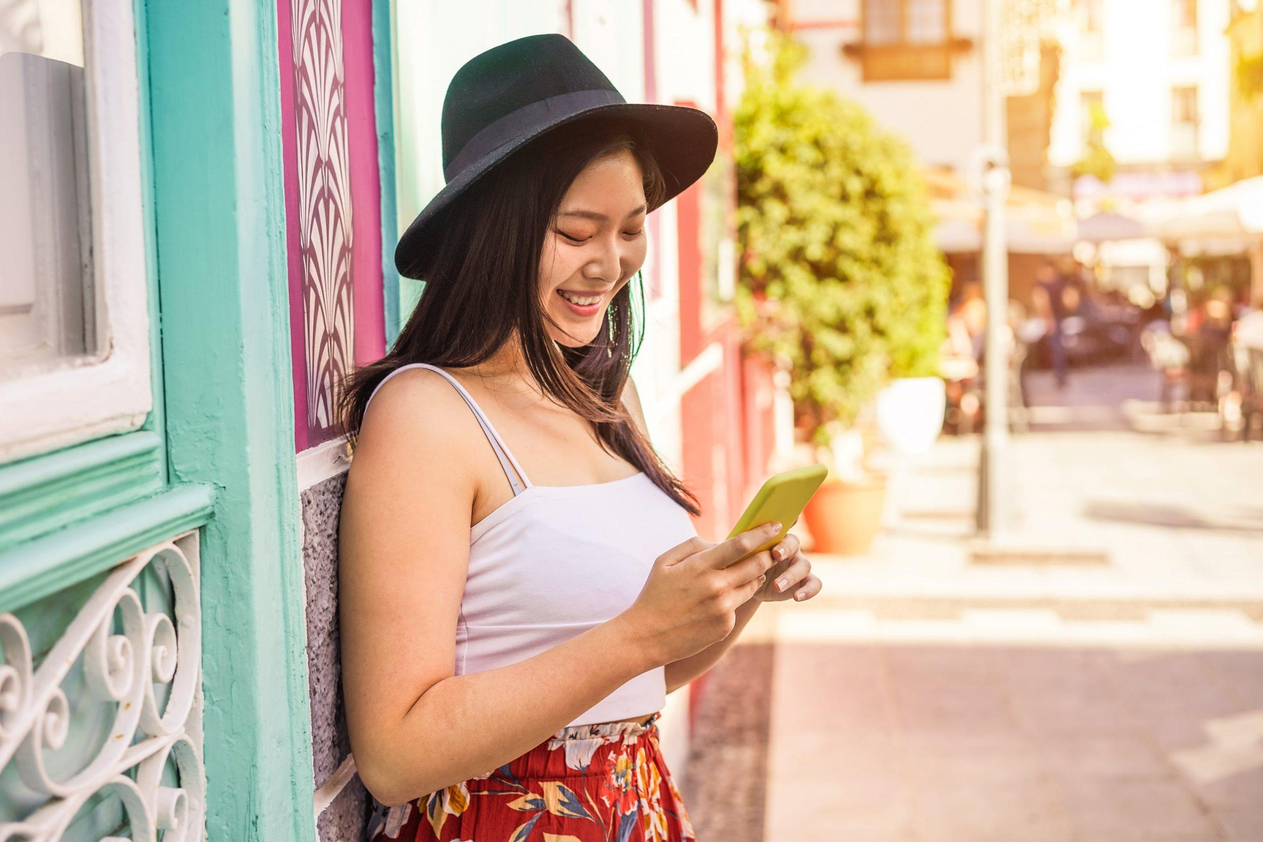 Influencer-usa-su-movil-en-exteriores-las-mejores-horas-para-publicar-en-redes-sociales