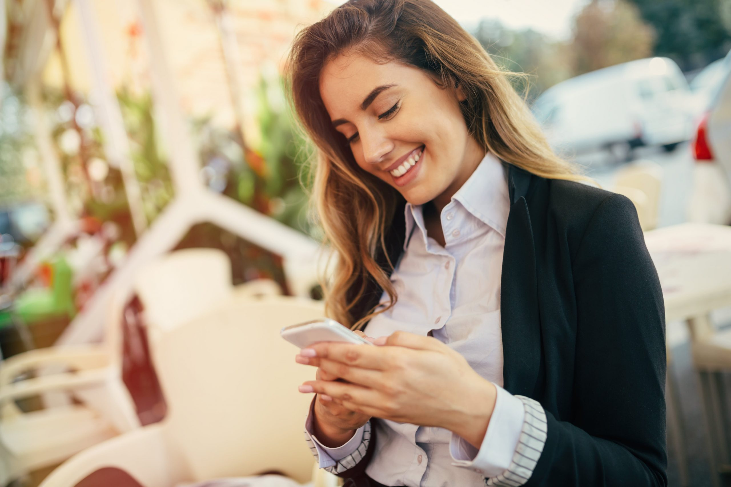 Mujer de negocios usa móvil sonriendo las mejores horas para publicar en redes sociales